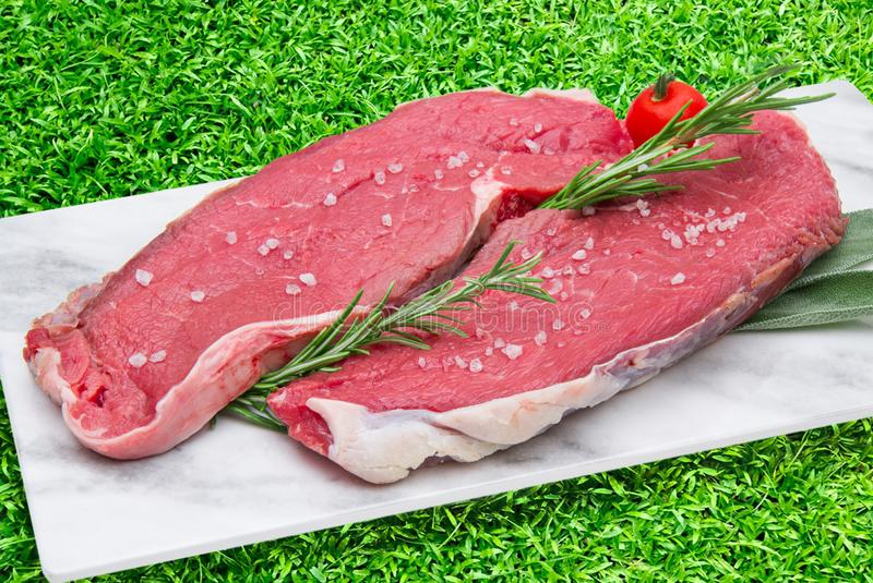 在白色盘的未加工的牛排肉有绿草背景 库存照片