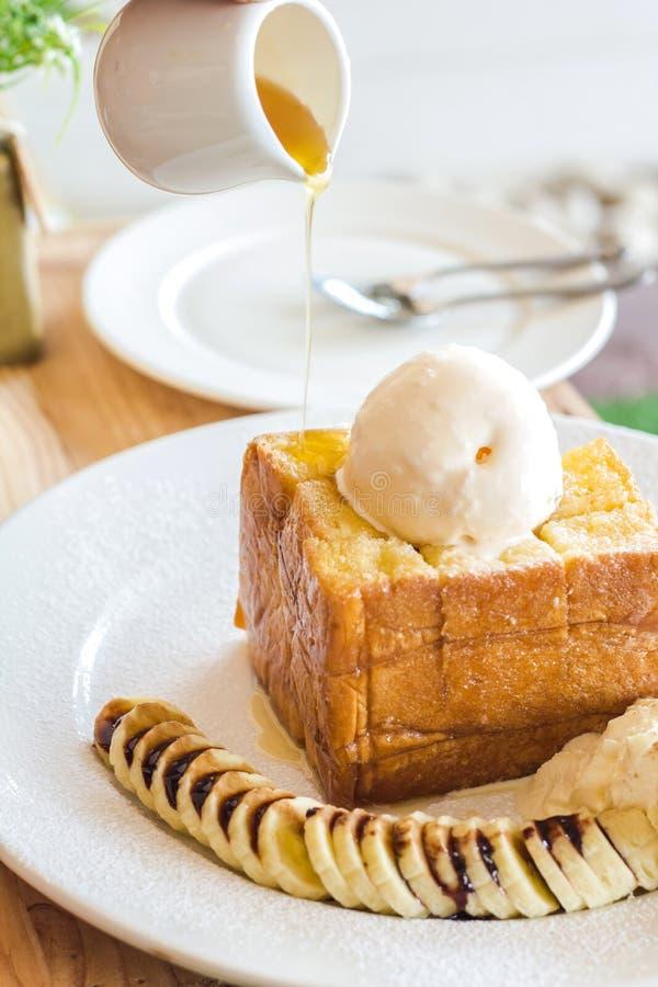 在白色盘的蜂蜜黄油多士食谱白面包在木头 图库摄影