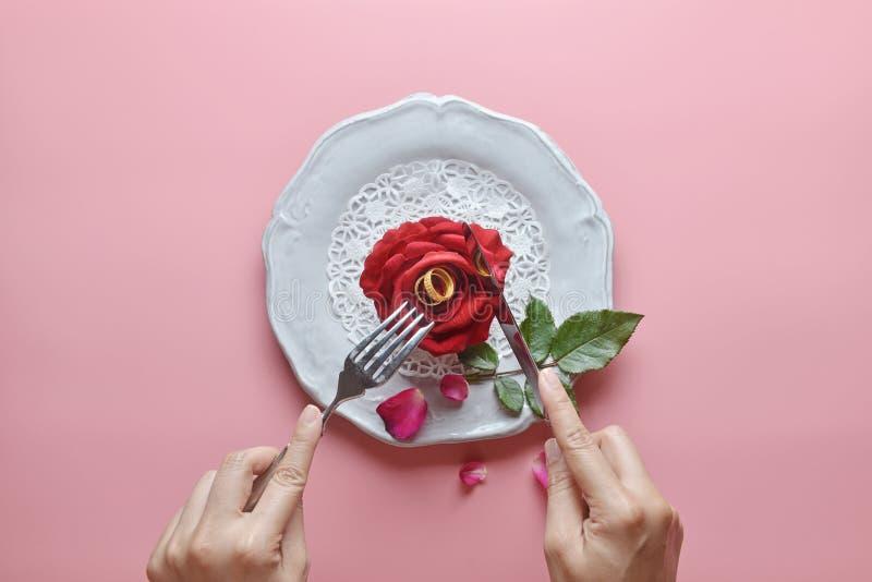 在白色盘,里面情侣戒指的红色玫瑰,与手藏品叉子和刀子,在桃红色背景,情人节的概念 免版税库存照片