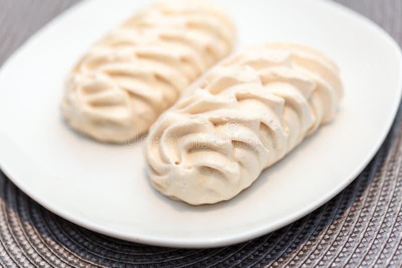 在白色盛肉盘的两装饰蛋白甜饼 库存照片