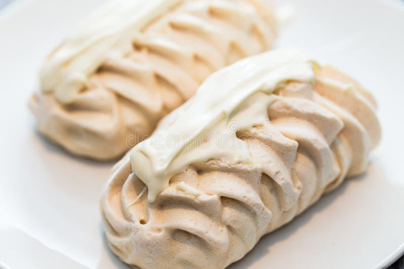 在白色盛肉盘的两装饰蛋白甜饼 免版税库存图片