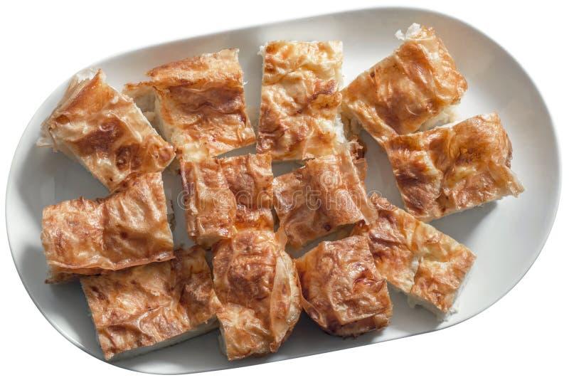 在白色盛肉盘的塞尔维亚传统Gibanica乳酪饼切片 免版税库存照片