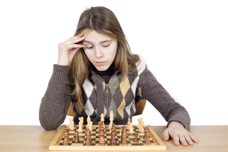 在白色看下来棋枰和强烈地考虑棋战略隔绝的沉思女孩演播室射击 免版税库存图片