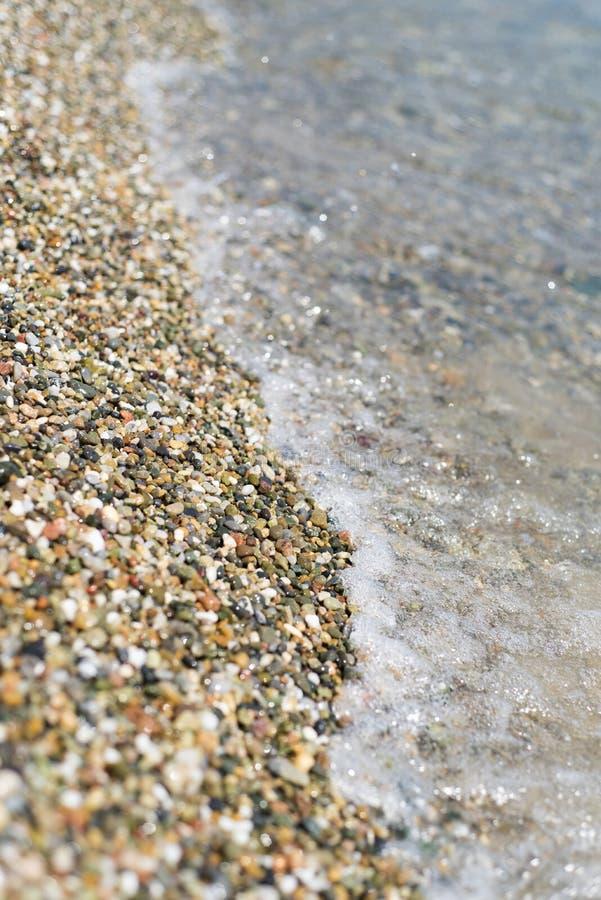在白色石海滩的水边缘 免版税库存图片