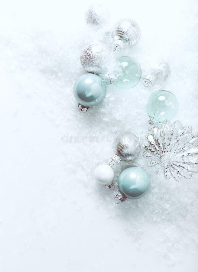 在白色石背景的圣诞节球与雪 免版税库存图片