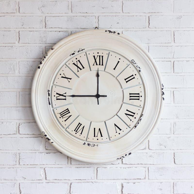 在白色砖墙上的葡萄酒时钟 免版税库存图片