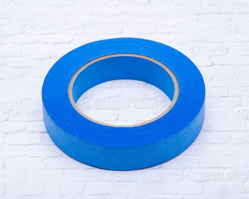 在白色砖墙上隔绝的多表面的蓝色画家的磁带 库存照片