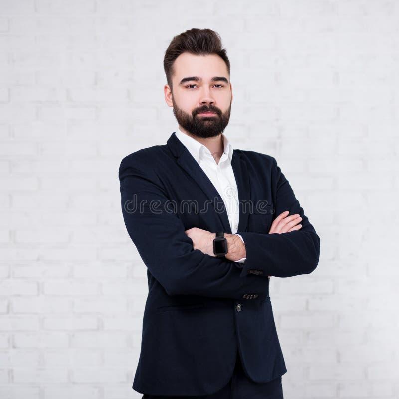 在白色砖墙背景的年轻有胡子的商人 免版税库存图片