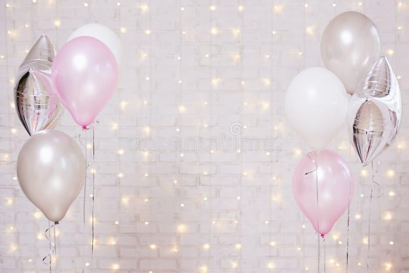 在白色砖墙背景的气球与光 免版税库存照片