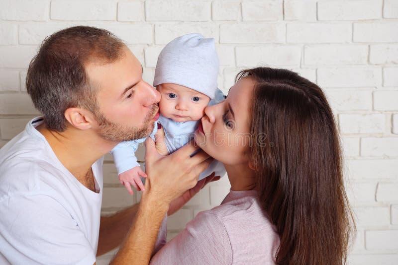 在白色砖墙附近的帅哥和迷人的妇女亲吻的甜婴孩身分 免版税库存照片