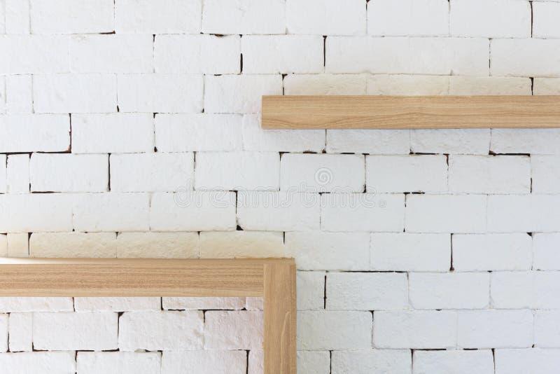 在白色砖背景的布朗木框架 库存照片