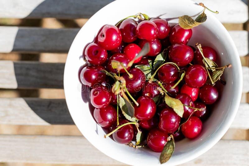 在白色碗特写镜头的新鲜的樱桃莓果 背景用莓果 在木的有机成熟红色樱桃莓果 库存图片