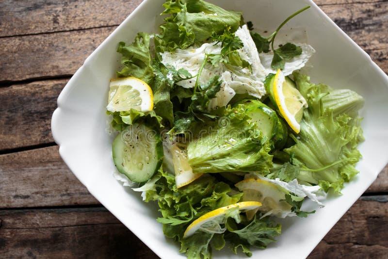 在白色碗的新鲜的沙拉在木背景 免版税图库摄影
