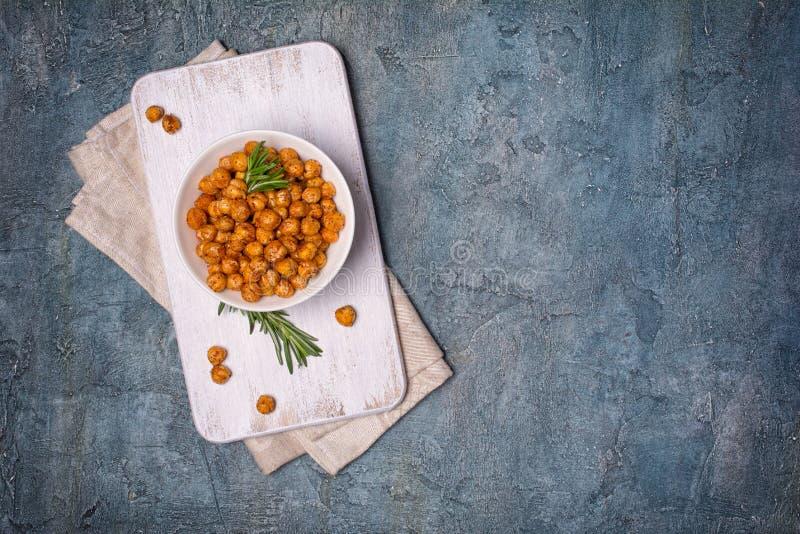 在白色碗的烤咸和辣鸡豆用迷迭香 免版税库存图片