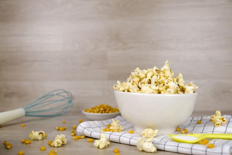 在白色碗的玉米花有淡色匙子、盐、手搅拌器和玉米种子的在木背景 烹调党的 图库摄影