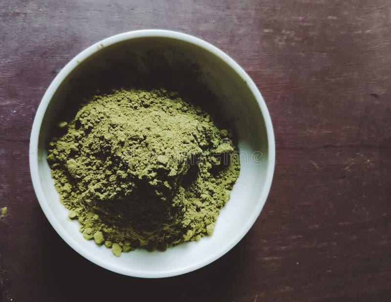 在白色碗的绿茶粉末在木桌上 库存图片