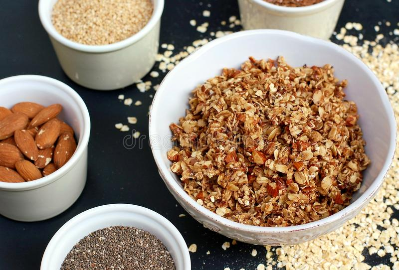 在白色碗的自创格兰诺拉麦片用杏仁和种子在黑背景 免版税库存图片