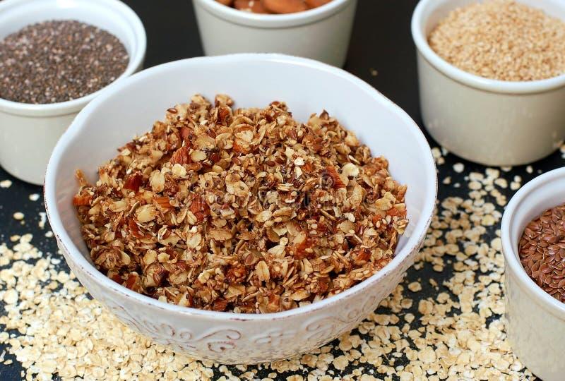 在白色碗的自创格兰诺拉麦片用杏仁和种子在黑背景 免版税图库摄影