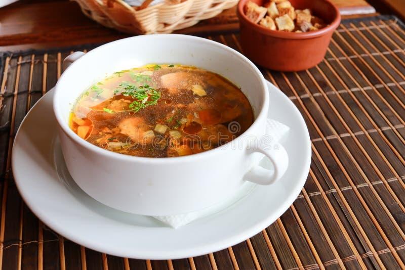 在白色碗的蘑菇汤用油煎方型小面包片 关闭上色百合软的查阅水 免版税图库摄影