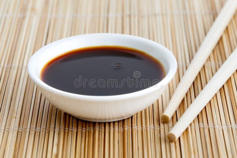 在白色碗的酱油在有木筷子的竹席子 库存照片