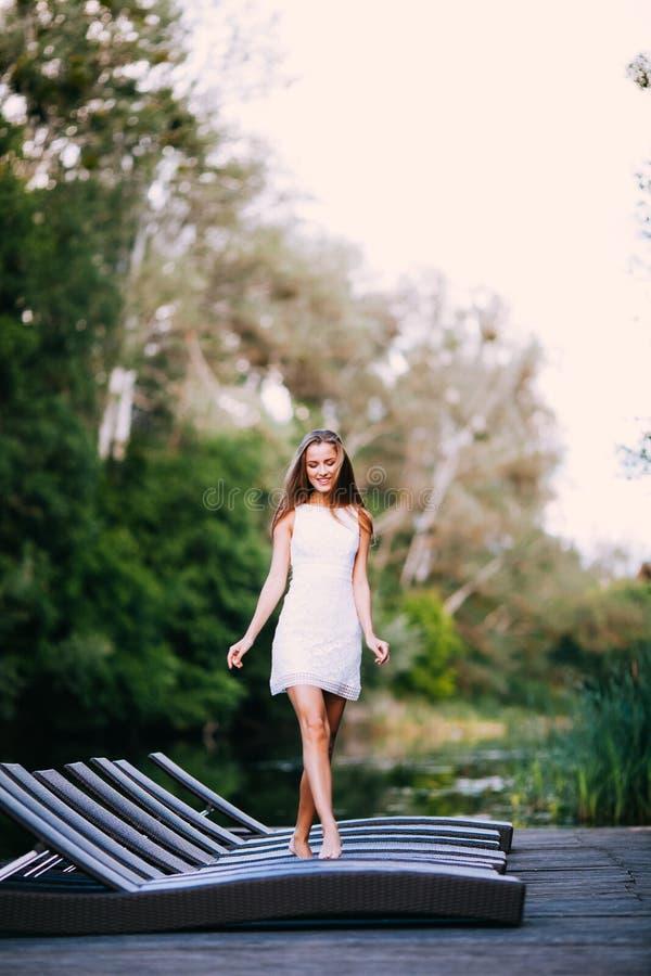 在白色礼服步行的迷人的长发微笑的愉快的深色的女孩有吸引力的模型由河 免版税库存照片