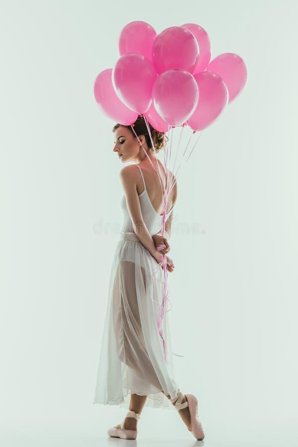 在白色礼服的典雅的跳芭蕾舞者有桃红色气球的 库存照片