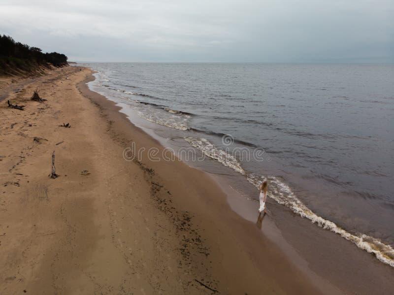 在白色礼服的空中美丽的幼小白肤金发的妇女海滩若虫在有波浪的海附近在愚钝的阴沉的天气期间与 库存照片