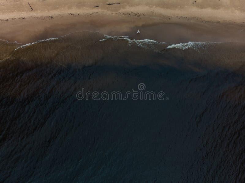 在白色礼服的空中美丽的幼小白肤金发的妇女海滩若虫在有波浪的海附近在愚钝的阴沉的天气期间与 图库摄影