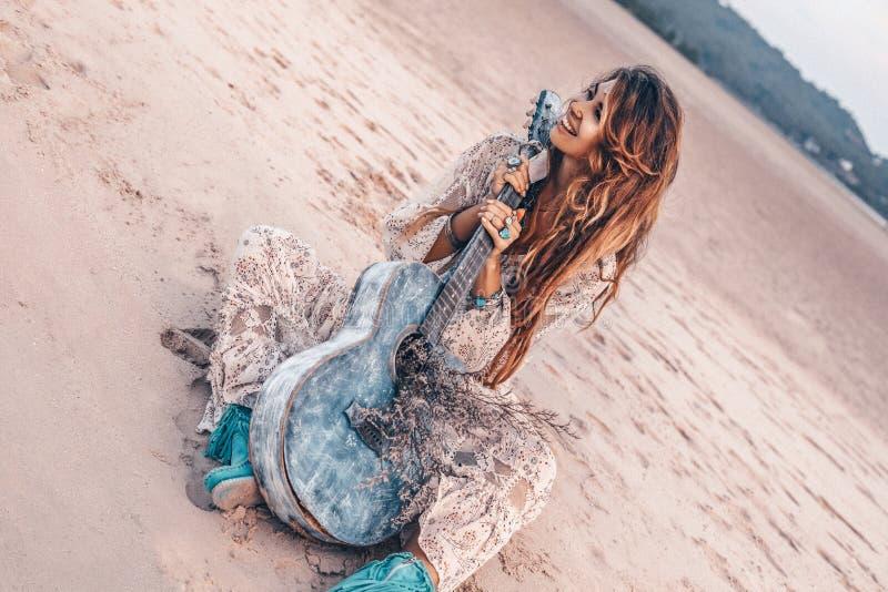 在白色礼服的美好的年轻快乐的时装模特儿有吉他的获得乐趣户外在日落 免版税库存图片