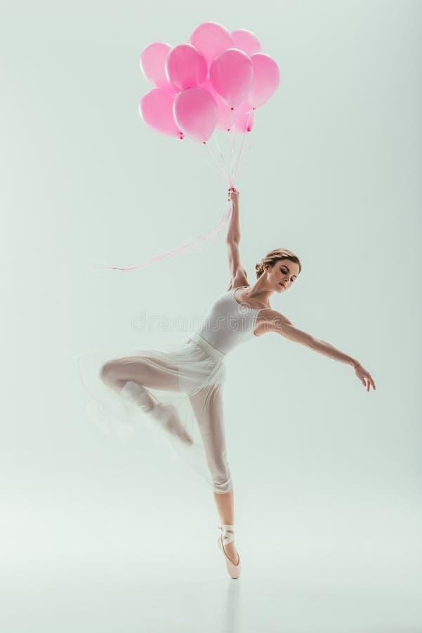 在白色礼服跳舞的跳芭蕾舞者与桃红色气球 免版税库存照片