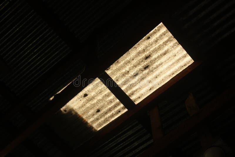 在白色窗口黑暗后的光 库存图片