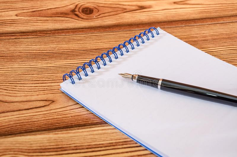 在白色笔记薄的黑笔以一张木桌为背景 r 免版税库存照片