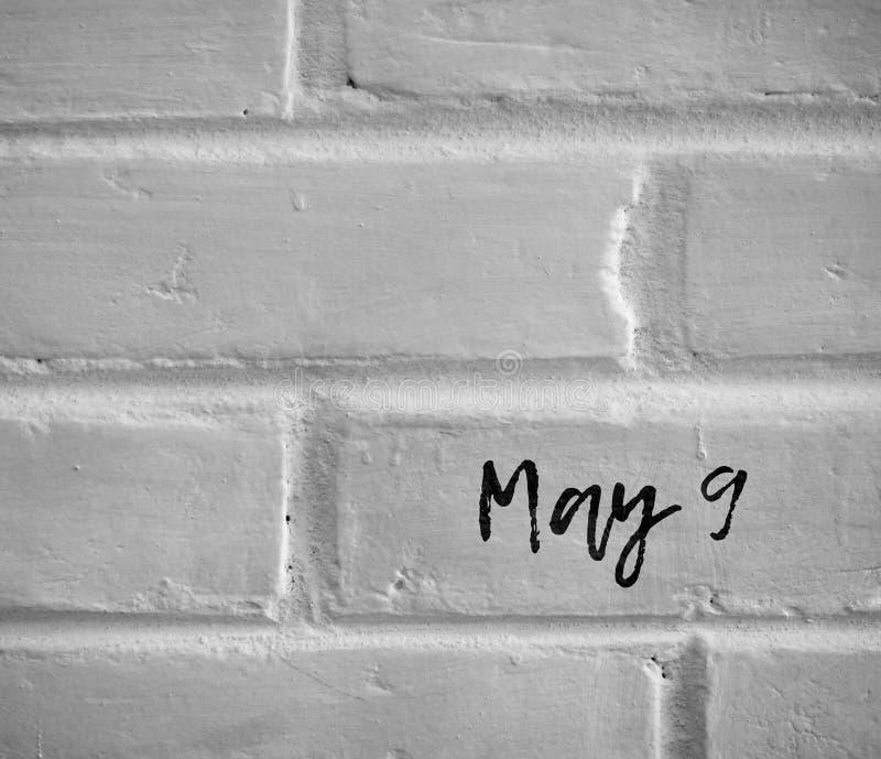 `在白色简单的砖墙写的5月9日` 免版税库存照片