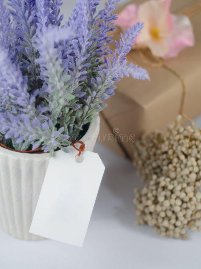 在白色罐的紫色淡紫色,当空白的标记纸被安置在花和礼物盒旁边 库存照片