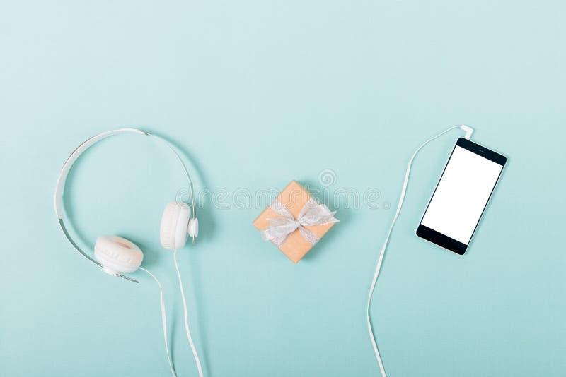 在白色耳机和被连接的智能手机附近的小礼物盒 免版税库存图片