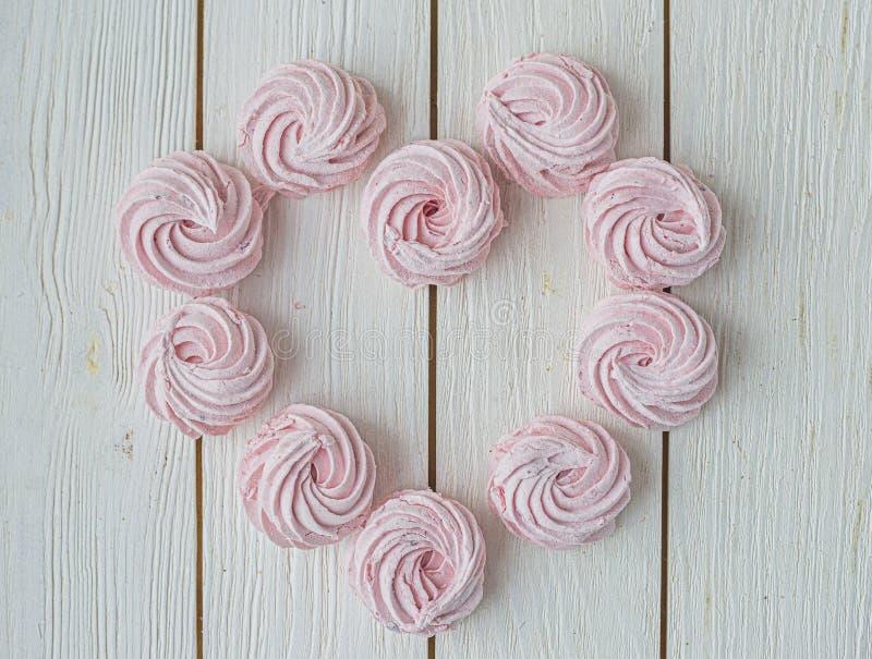 在白色背景上以心形排列 平铺 顶视图 粉红的甜自制莪术或棉花糖 多彩 免版税库存图片