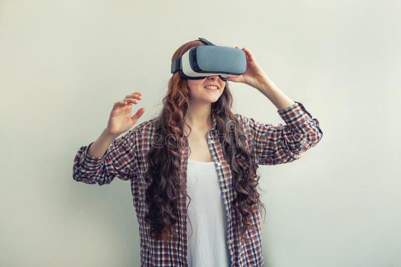 在白色背景上戴虚拟现实眼镜头盔的少女微笑 使用 免版税图库摄影