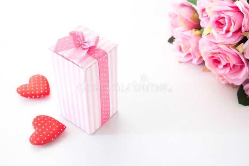 在白色背景与桃红色玫瑰和心脏的接近的礼物盒在白色 免版税库存图片