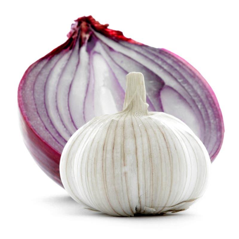 在白色背景与红洋葱一半的整个大蒜隔绝的 免版税库存图片