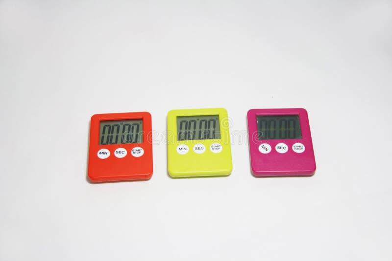 在白色背景可利用的桔子的三塑料秒表,黑暗桃红色和绿色 图库摄影