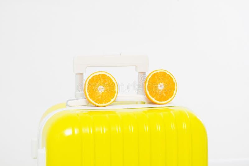 在白色背景和两个切片桔子隔绝的手提箱 复制空间 免版税图库摄影