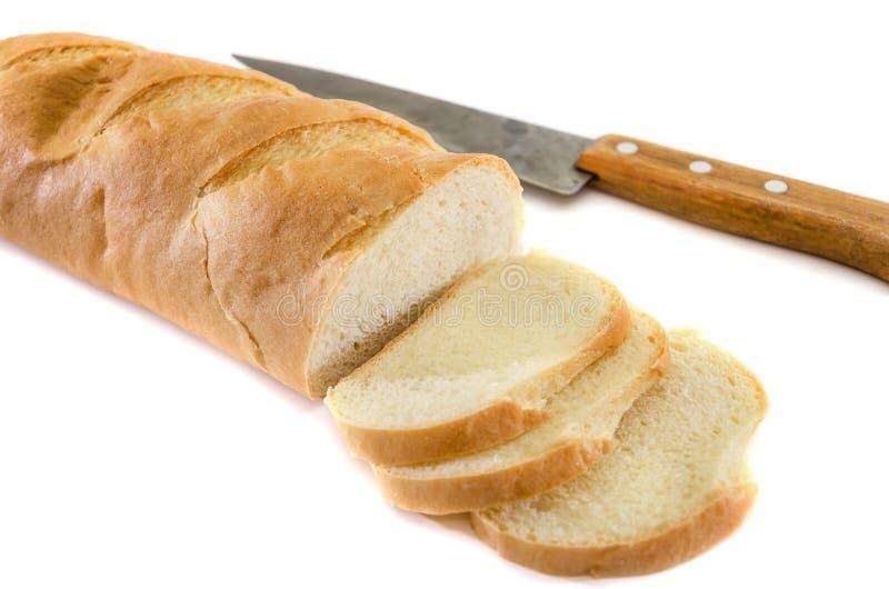 在白色背景和刀子隔绝的大面包 可口乌克兰面包 被切的面包片 免版税库存图片
