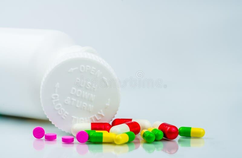 在白色背景和塑料瓶的五颜六色的药片有空白的标签和拷贝空间的 能防止孩童瞎摸弄包装 儿童抗性药片 免版税库存图片
