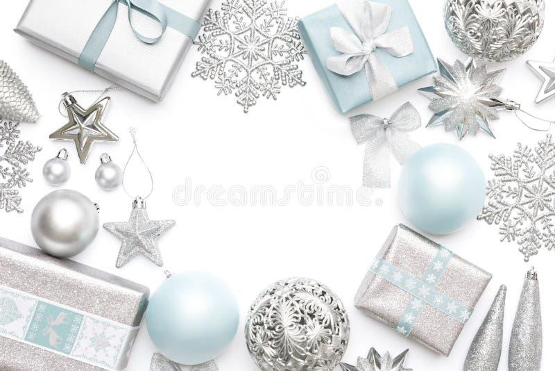 在白色背景和淡色蓝色圣诞节礼物、装饰品和装饰隔绝的银 背景边界把空白圣诞节礼品金黄查出的丝带装箱 免版税库存照片