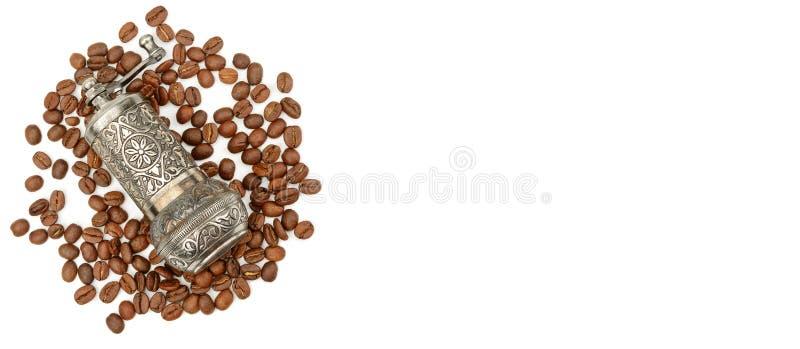 在白色背景和烤咖啡豆隔绝的磨咖啡器 r r r 库存图片