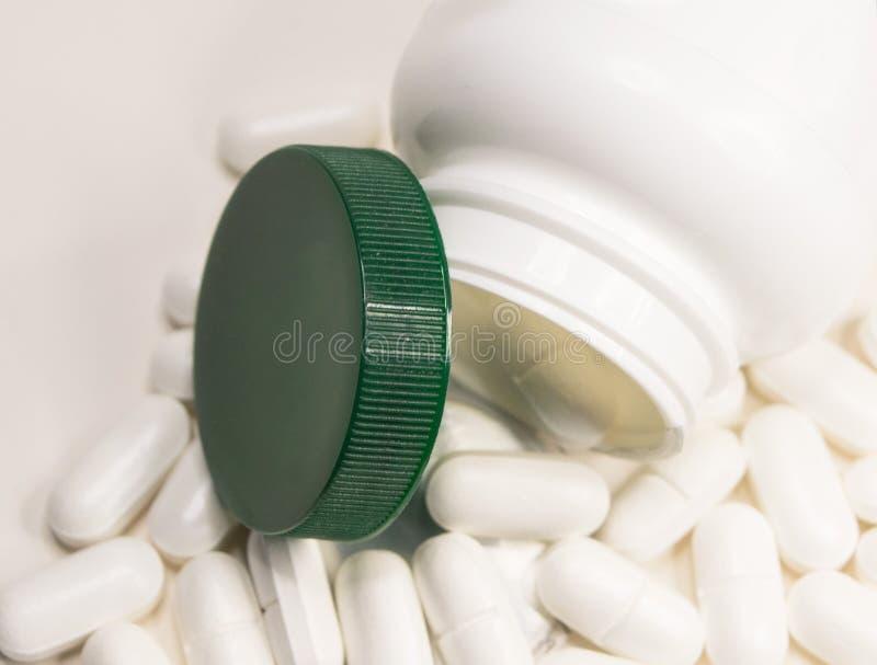 在白色背景和白色药片驱散的特写镜头瓶子 库存照片