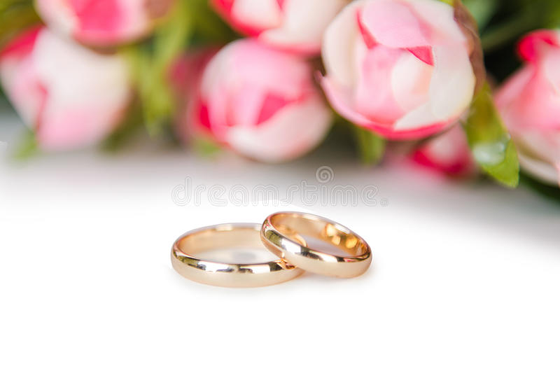 在白色背景和花隔绝的婚戒 免版税库存照片