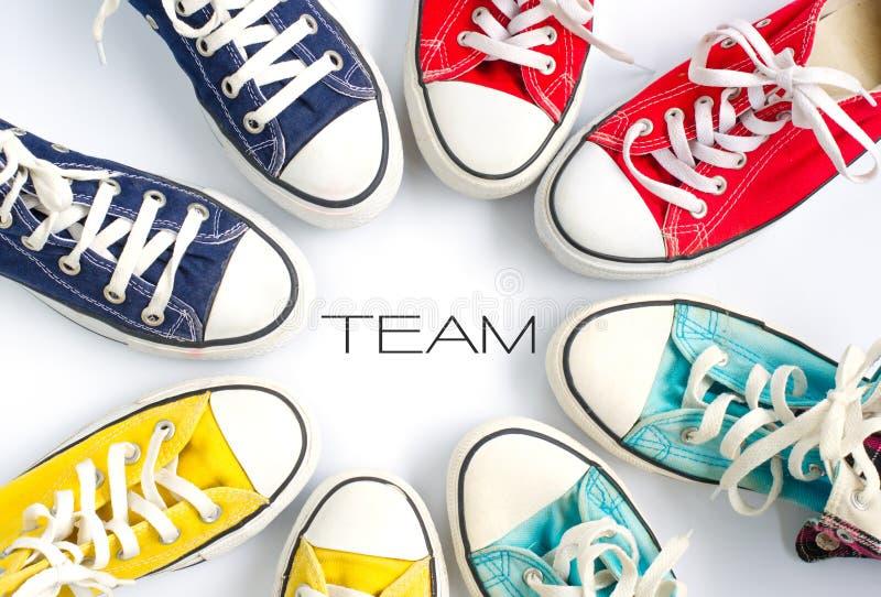 在白色背景和词`队`概念队的多彩多姿的运动鞋运转 库存照片