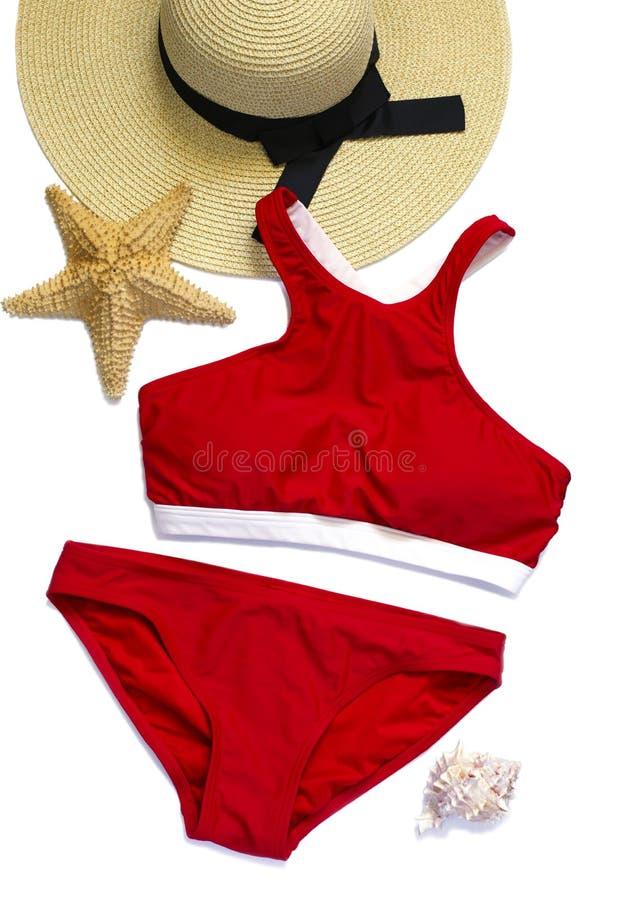 在白色背景和贝壳隔绝的妇女的泳装、草帽 夏天时尚的平的被放置的构成 免版税库存图片