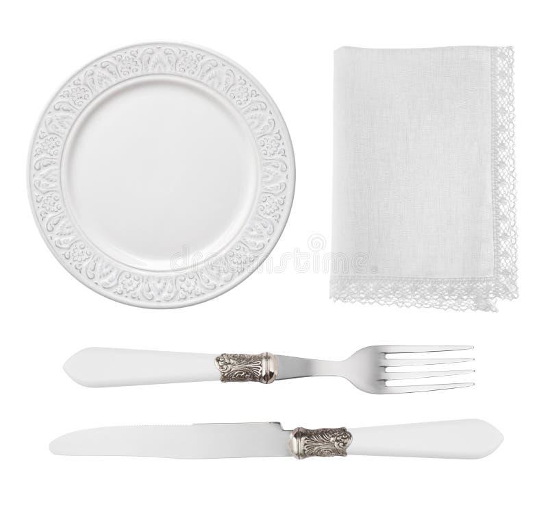 在白色背景和餐巾隔绝的葡萄酒板材、刀子、叉子 免版税库存照片